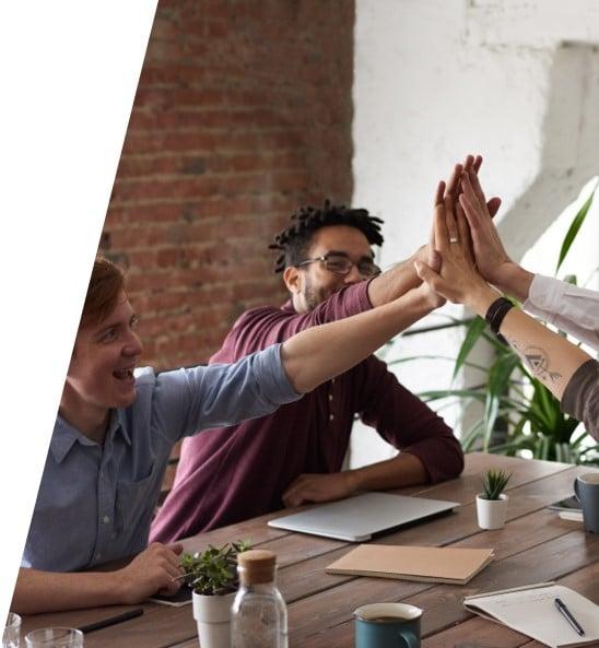 Mitarbeiter geben sich ein High-Five in der Gruppe