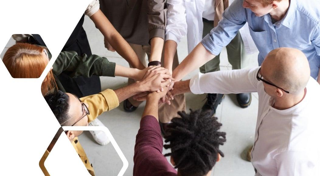 Mitarbeiter im Kreis legen Hände aufeinander